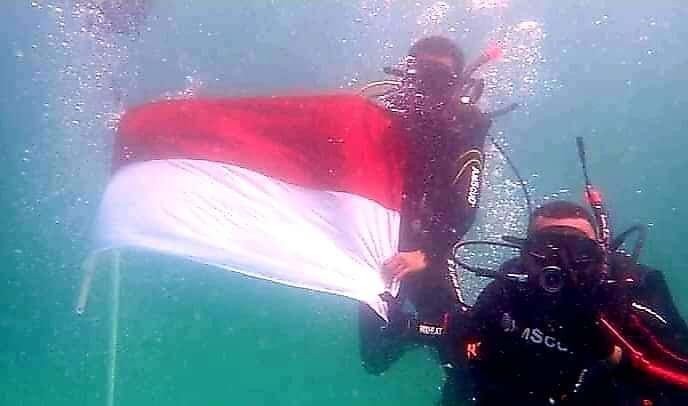 Bendera Merah Putih dibentangkan di atas permukaan laut, pengibaran di dasar laut, hinggga formasi api.