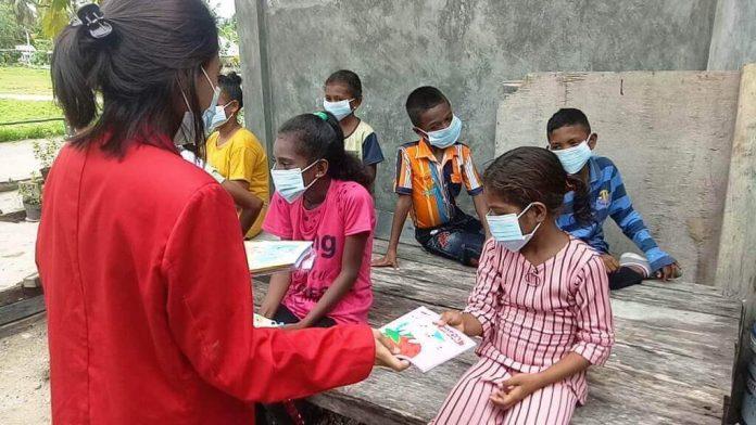 Natalia Christy Rahaded, mahasiswa Program Studi Akuntansi Untag Surabaya mengajarkan siswa-siswi Taman Baca tentang penerapan protokol kesehatan. Foto: Dokpri