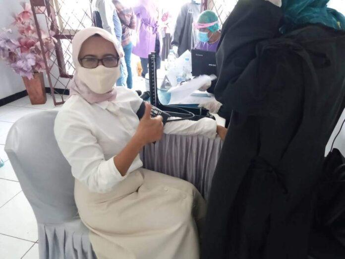 Kepala Dinas Perindustrian dan Perdagangan Kota Tual Darnawati Amir merupakan perempuan pertama penerima vaksin di Tual. Foto: Fredy Jamrewav