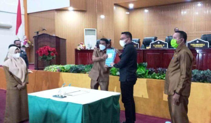 Usai menyampaikan nota pengantar, Sekda Tual Ahmad Yani Renuat menyerahkan dokumen laporan keterangan pertanggungjawaban kepada Ketua DPRD Kota Tual, Senin (12/4/2021). Foto: Ludwiena Maturbongs